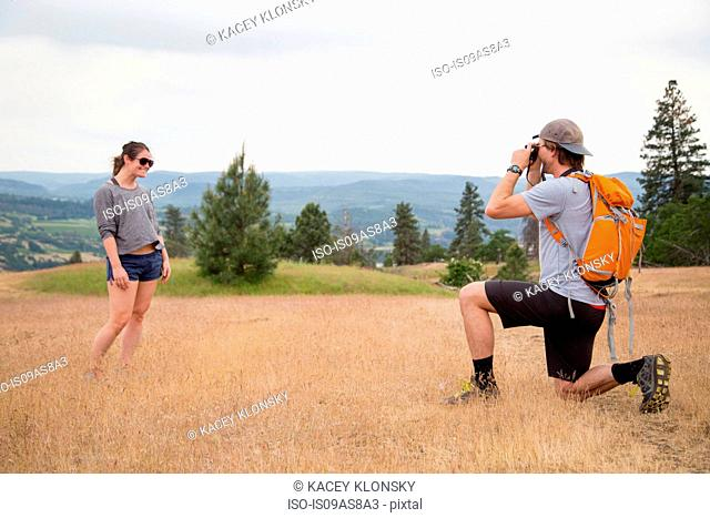 Young man taking photograph of young woman in rural setting