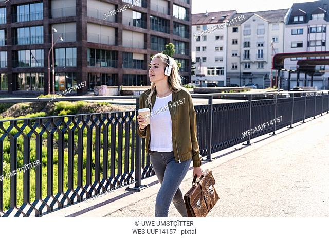 Young woman walking on bridge, drinking coffee, listening music with headphones