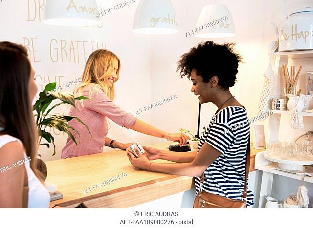 Young woman making purchase in shop
