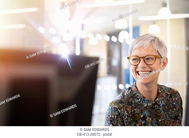 Enthusiastic senior businesswoman looking away in office