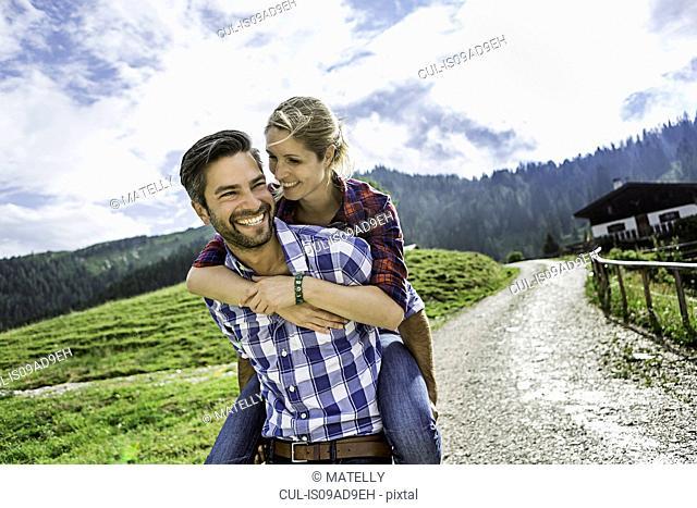 Woman riding piggyback on man, Tirol, Austria