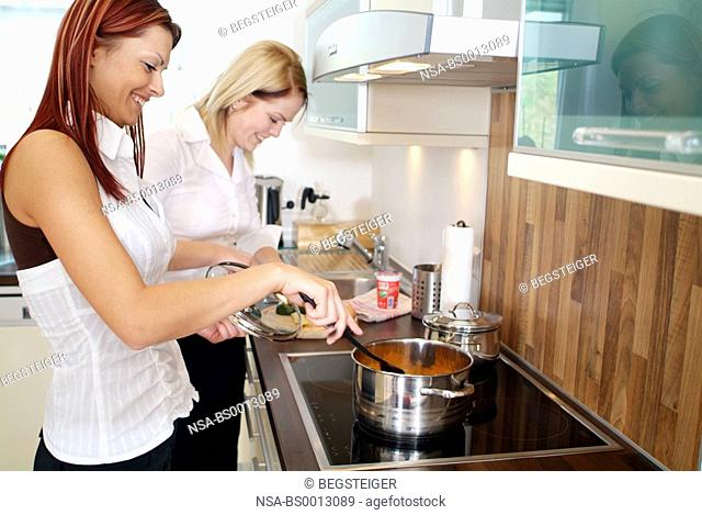 two young women cooking together