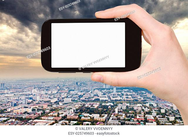 travel concept - hand holds smartphone with cut out screen and storm clouds over city on background