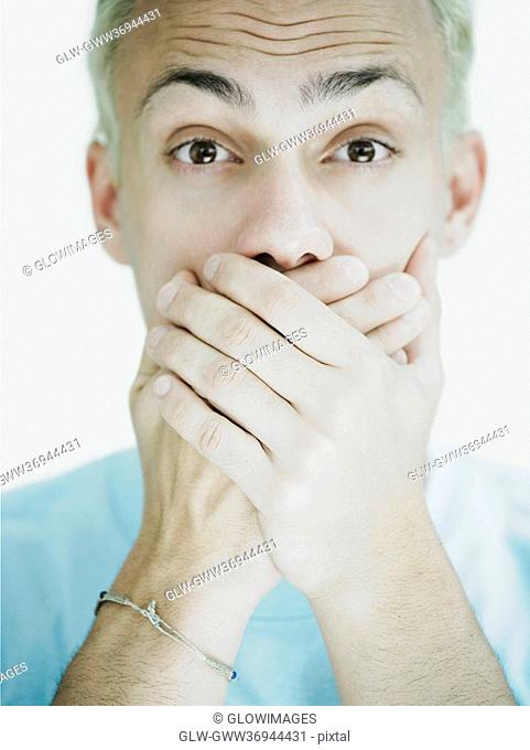 Portrait of a young man covering his mouth with his hands