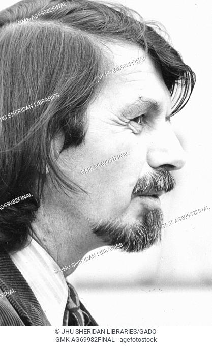 Head-shot of poet Robert Creeley, wearing a dark corduroy jacket and a striped shirt, profile shot of the right side of his face, has a graying beard