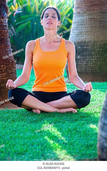Woman sitting, meditating, outdoors
