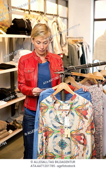Woman in a boutique is frightened about the price