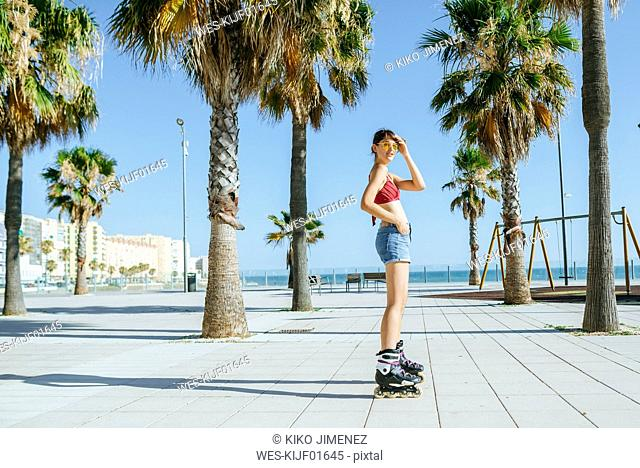 Young woman on inline skates on boardwalk with palm trees