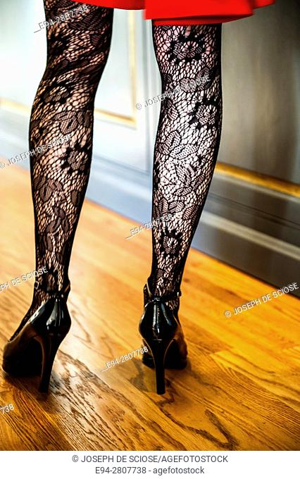 Close up of woman's legs wearing lace stockings, high heels and a red dress standing on wood flooring in a home