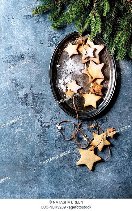 Homemade shortbread star shape sugar cookies different size with sugar powder on thread in vintage metal tray with fir branches over blue texture surface