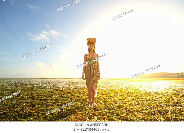 Pacific Islander woman balancing basket on head in rice paddy