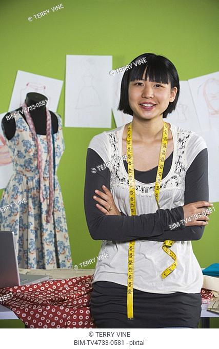 Portrait of Asian seamstress in shop