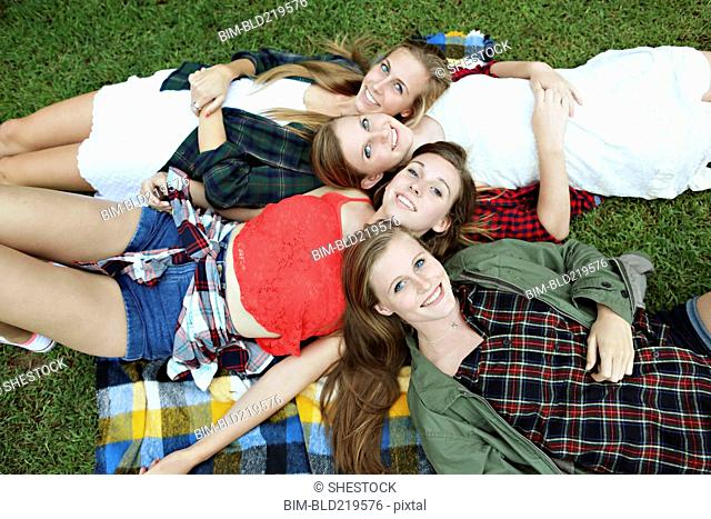 Smiling women laying on blanket in grass