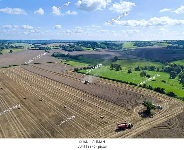Aerial view of summer country farming landscape and wheat field being harvested by combine harvester