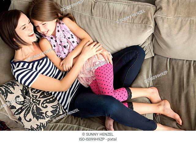 Mid adult woman laughing with daughter on sofa