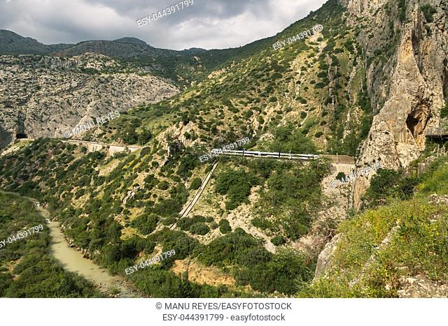 Train crossing a tunnel in a large valley in ardales, andalucia, surrounded by hills and a river