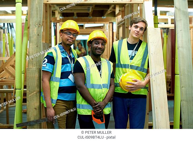 Three male higher education carpentry students in college workshop, portrait