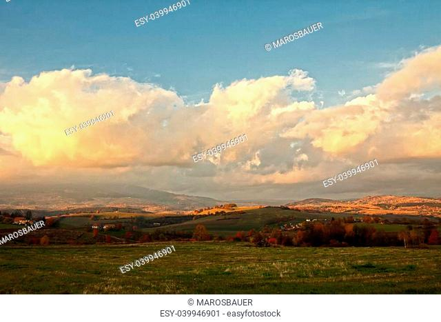 Autumn landscape with trees, meadows and mountains by sunset