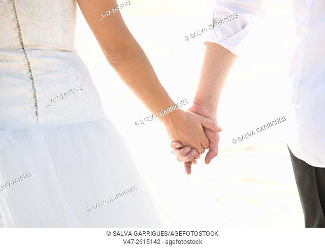 Wedding couple holding hands on their wedding day