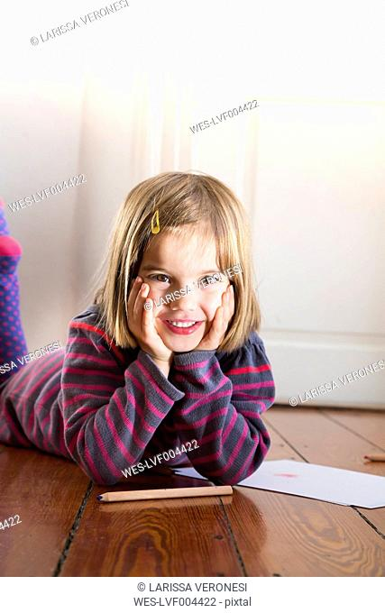 Portrait of little girl lying on the floor with paper and coloured pencils