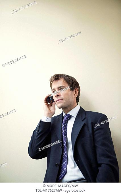 A businessman leaning against a wall using a smartphone