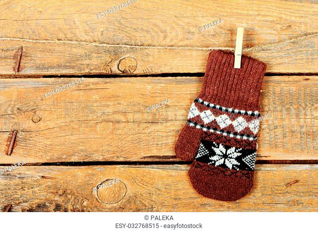 One brown mitten with ethnic ornament on old wooden background