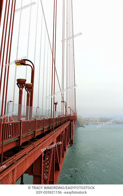 A view of the side of the Golden Gate Bridge, Marin County and the Pacific Ocean from a viewing area on the Golden Gate Bridge on a foggy, smog filled day
