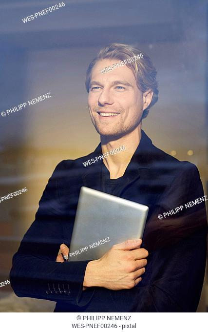 Portrait of smiling young businessman with tablet behind windowpane