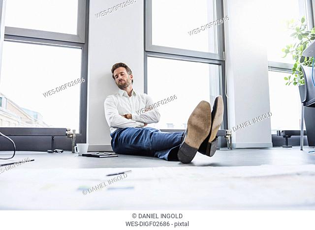 Businessman relaxing on the floor of his office