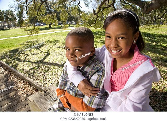 Portrait of young African American boy and girl outdoors sitting in park, looking at camera