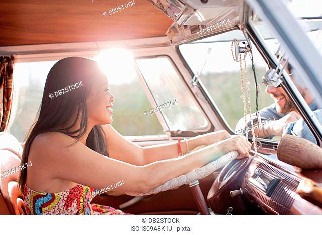 Young woman in camper van and smiling at boyfriend