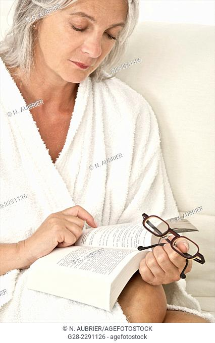 Beautiful senior woman sitting on a sofa and reading a book and holding a pair of glasses in her hand