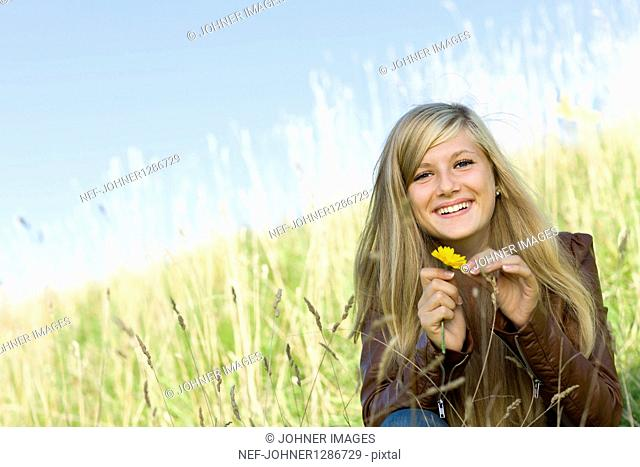 Portrait of girl holding marigold in field, smiling