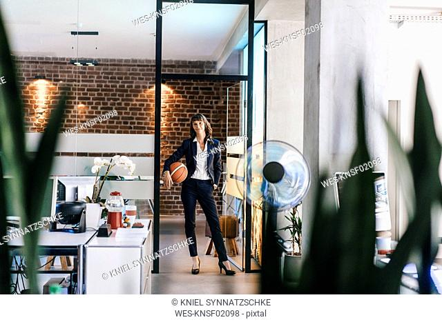 Businesswoman holding basket ball in office