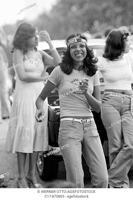 Seventies, black and white photo, people, young girl dances on the street, headband, Brazilian, carnival, Brazil, Minas Gerais, Belo Horizonte