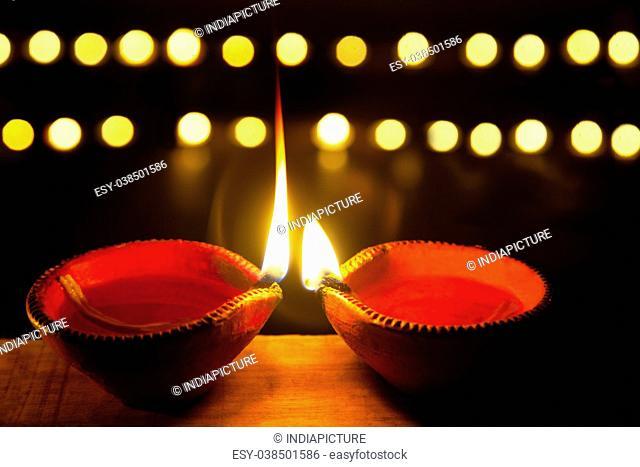 Two earthen lamps lit for festival