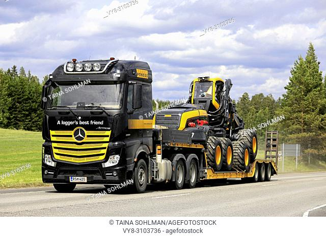 Mercedes-Benz Actros 3363 semi in Ponsse Plc colors black and yellow transports Scorpion Forest harvester in summer. Uurainen, Finland - June 15, 2018