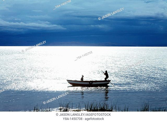 Two boys in a small boat on Lake Titicaca, silhouetted by the setting sun with dark storm clouds in the distance  Llachon, Capachica Peninsula, near Puno, Peru