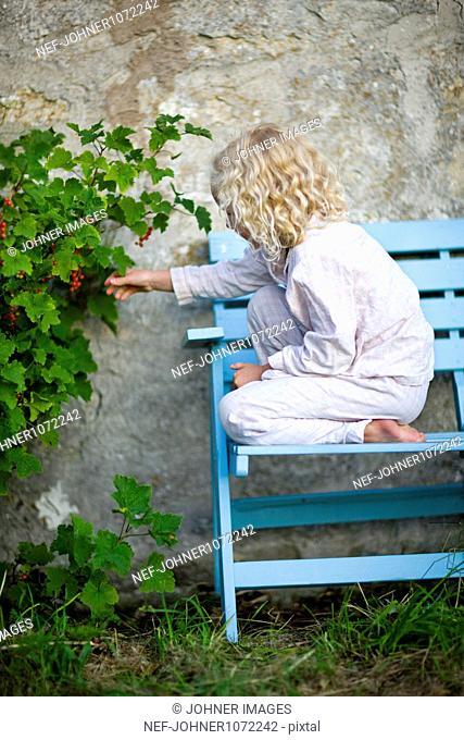 Blonde girl on blue bench