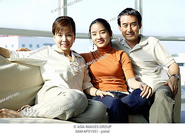 Family with one daughter sitting side by side on sofa
