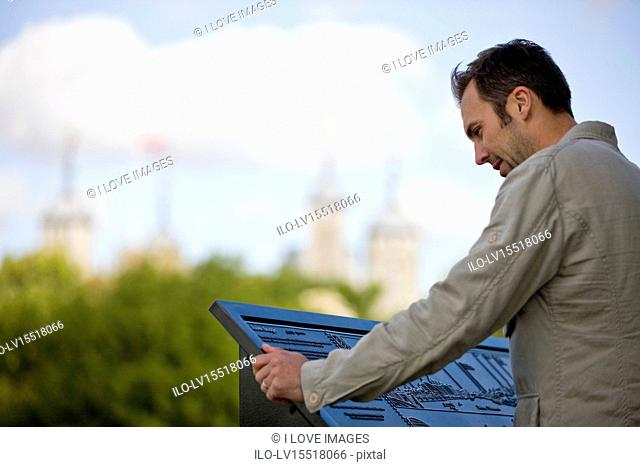 A mid-adult man standing in front of the Tower of London, looking at a map