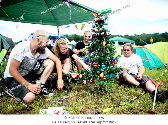 21 June 2019, Lower Saxony, Scheeßel: Dennis (l-r), Michelle, Alexander and Daniel sit on the campground of the Hurricane Festival around a Christmas tree...