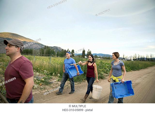 Workers carrying pail and crates on farm