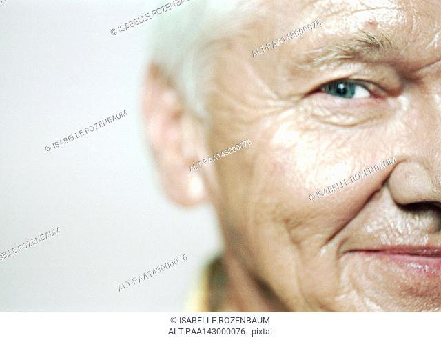 Senior man looking at camera, close-up, partial view
