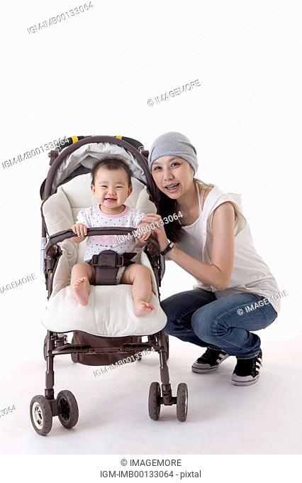 Mother crouching near the baby carriage and smiling at the camera