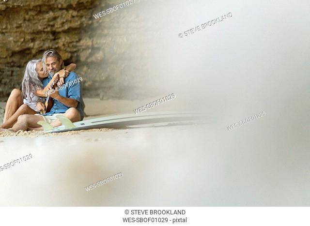 Handsome senior couple sitting on the beach, man playing guitar