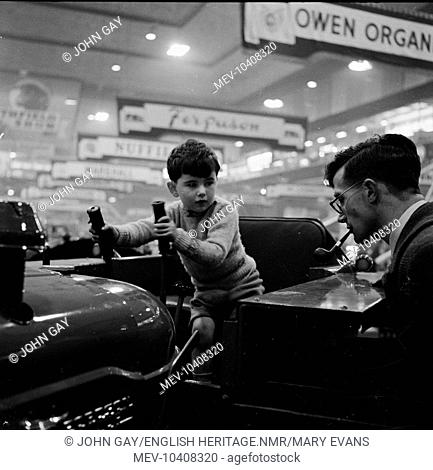 A young boy on a Fordson tractor, with a man at the side smoking a pipe, at the Royal Smithfield Show at Earls Court