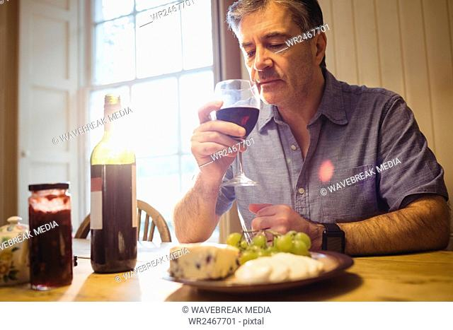 Mature man sitting at table and tasting red wine
