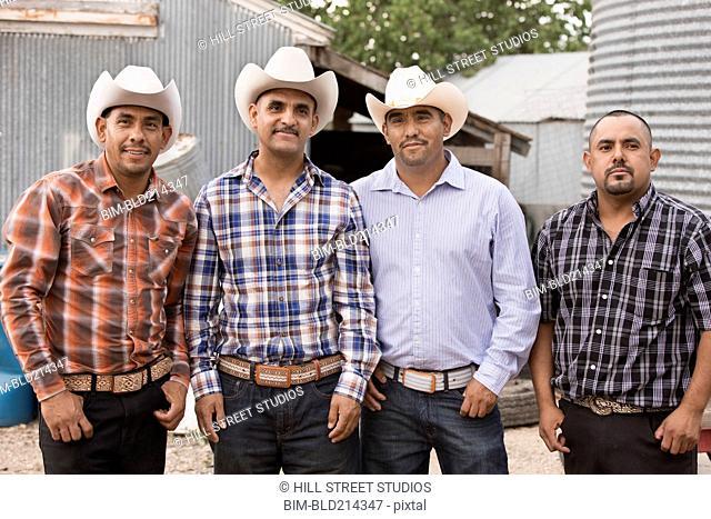 Hispanic men wearing cowboy hats on ranch