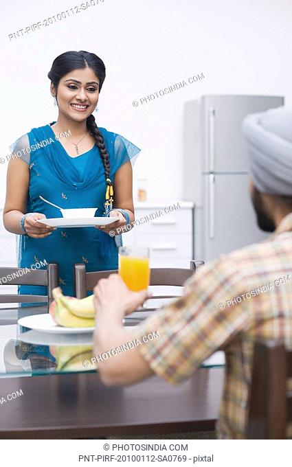 Woman serving breakfast to her husband
